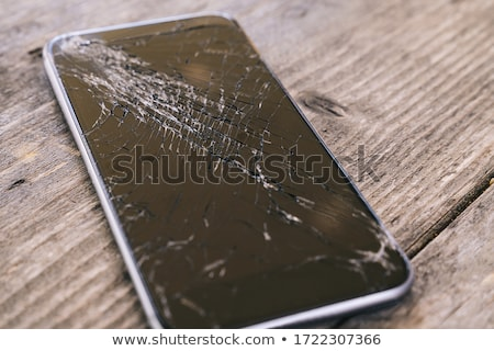 Smartphone display with broken glass on a wodden table Stock photo © galitskaya