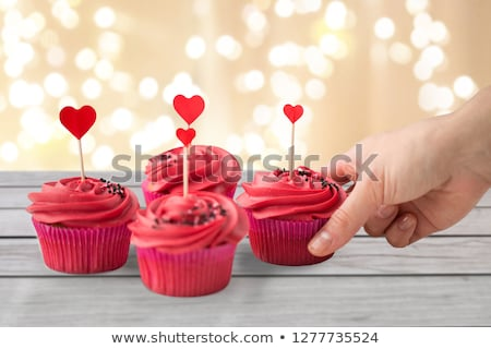 close up of hand taking cupcakes with heart sticks stock photo © dolgachov