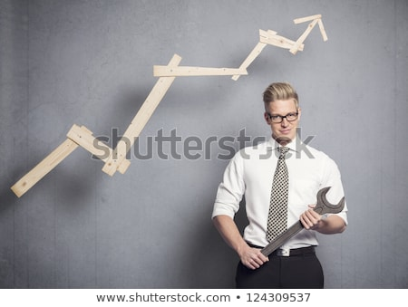 Confident businessman with wrench and graph. Stock photo © lichtmeister