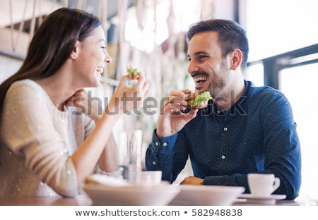 Two couples enjoying food and drink in a restaurant Stock photo © Kzenon