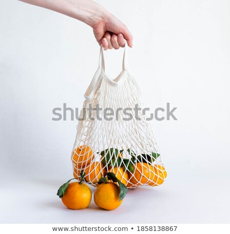 man and reusable mesh bag with oranges