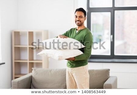 indian man with sofa cushions at new home Stock photo © dolgachov