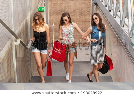 group of three beautiful girls sitting on stairs at shopping mal stock photo © hasloo