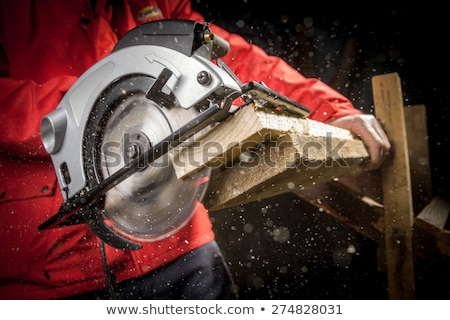 Stock photo: carpenter with a circular saw