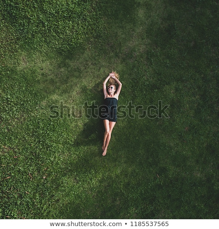 Young pretty woman lying on the grass and smiling at summer sunset Stock photo © photocreo