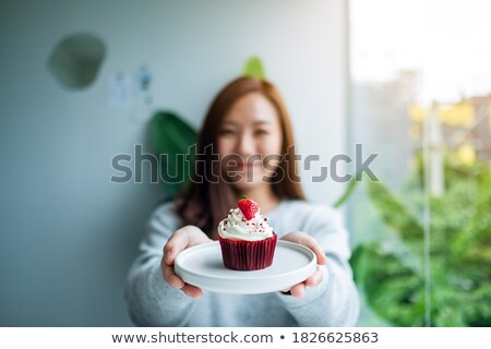 Gourmet. Happy Young Woman holding Cupcake with Whipped Cream Stock photo © gromovataya