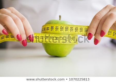 woman eating green apple and holding scales stock photo © hasloo