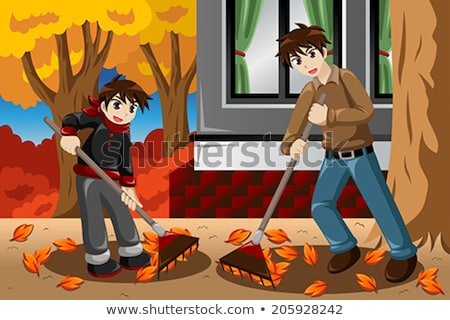 Father And Son Raking Leaves In The Yard During Fall Season Stockfoto © Artisticco