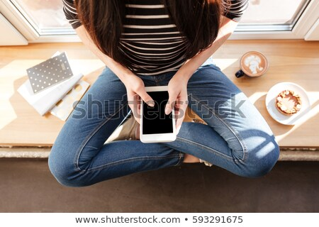 Top view of Asian woman with cake on windowsill Stock photo © deandrobot