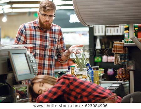 Confused man looking at sleeping cashier lady on workspace Stock photo © deandrobot