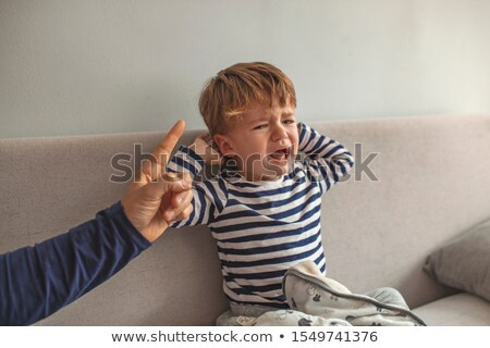 crying boy with his hand raised stock photo © traimak