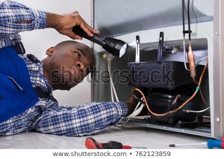 Handyman Checking Refrigerator With Flashlight Stock photo © AndreyPopov