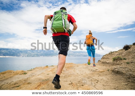 Trail running girl with backpack in mountains on rocky path Stock photo © blasbike