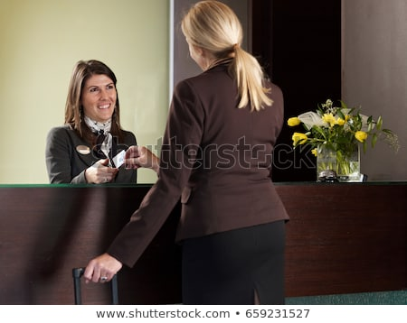 Business woman paying for her hotel room at front desk Stock photo © IS2