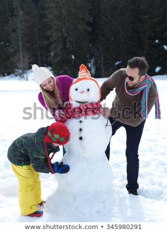 father and daughter making a snowman stock photo © is2