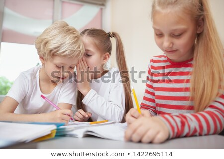 A schoolgirl whispers to her friend in a primary class Stock photo © monkey_business