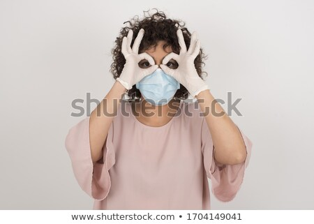 Young beautiful funny cheerful female doctor in medical mask and sterile gloves on white background Stock photo © Traimak