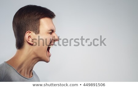 Portrait of an irritated young man standing Stock photo © deandrobot
