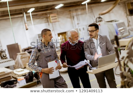three men standing and discuss in furniture factory stock photo © boggy