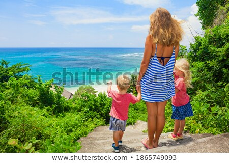 Mother and son go to the sea beach. Resort vacation on tropical beach. Path to beach stock photo © galitskaya