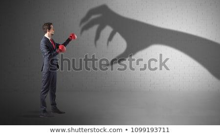 businessman fighting with scary hand shadow stock photo © ra2studio