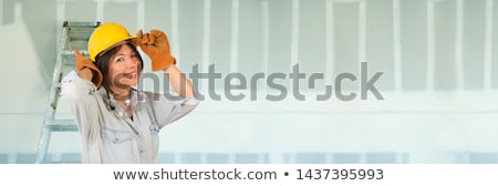 hispanic female contractor wearing hard hat against drywall bann stock photo © feverpitch