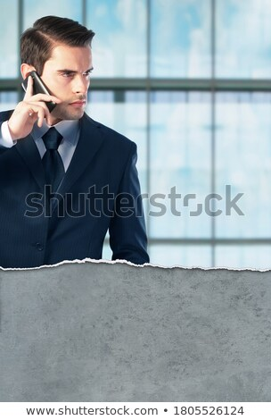 Young well-dressed businessman with smartphone listening to music Stock photo © pressmaster