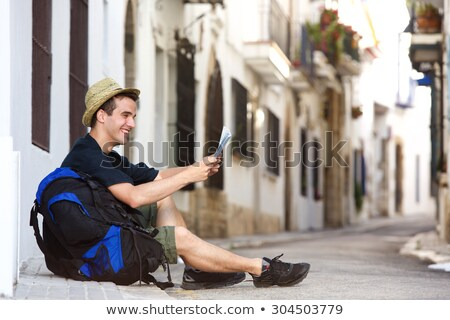 young man traveler with backpack sitting looking at the map rela stock photo © freedomz
