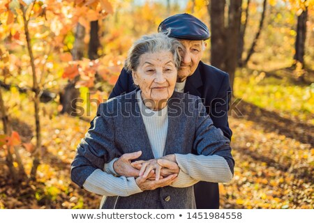 Happy senior citizens in the autumn forest. family, age, season and people concept - happy senior co Stock photo © galitskaya