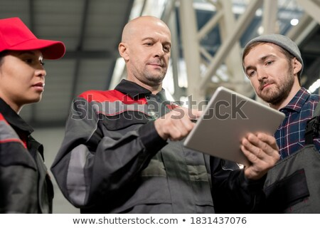 Two professional engineers in workwear discussing points of quality control Stock photo © pressmaster
