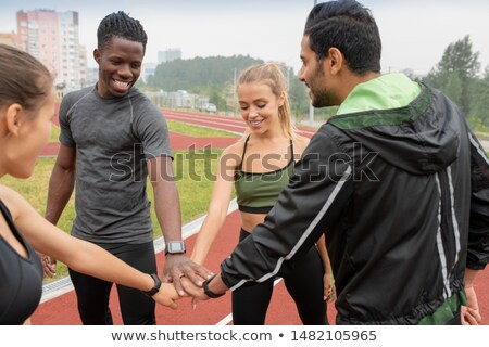 Young successful marathon participants in activewear making pile of hands Stock photo © pressmaster