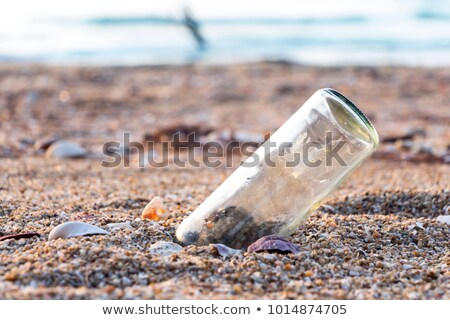 Bottle with a message or letter on the beach near seashell. SOS. Copy space. Stock photo © Illia