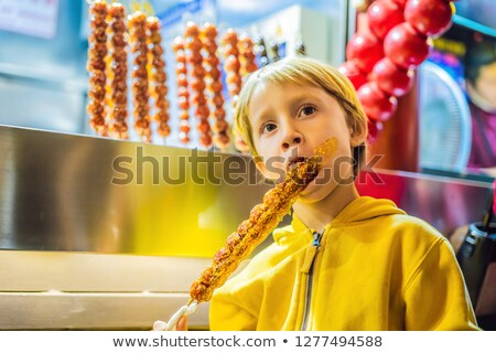 Boy eating Traditional Chinese Dessert - Candied Fruit on a Wooden Stick Stock photo © galitskaya