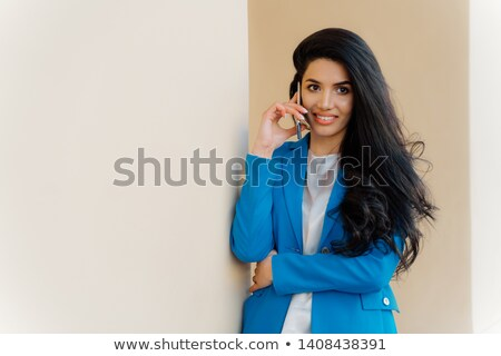Satisfied brunette business lady calls on smartphone device, books tickets for trip abroad, makes po Stock photo © vkstudio