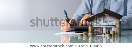 Man Calculating Tax By House Photo And Coins Stock photo © AndreyPopov