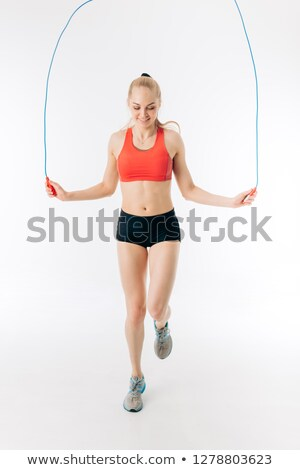 Photo of young happy woman doing exercise with jump rope and smiling Stock photo © deandrobot