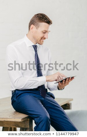 Pleased attractive young businessman checks email on portable pc, watches vidio on internet webpage, Stock photo © vkstudio