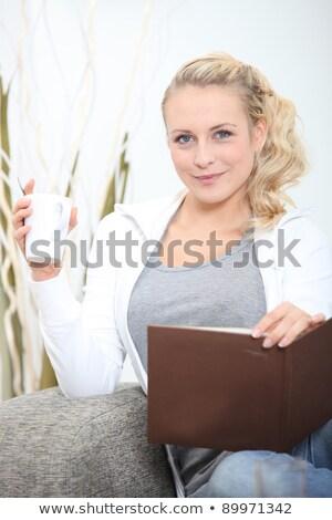 young woman sitting on sofa with photograph album and mug of coffee Stock photo © photography33