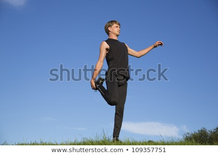 Stock photo: Sportsman trying stretch right leg crook behind
