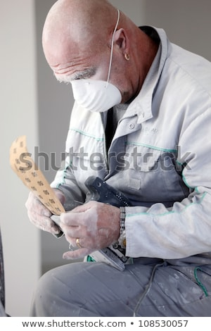 Decorator fitting sandpaper onto an electric sander Stock photo © photography33