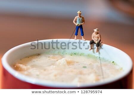 Figurine fisherman fishing in a soup mug. Stock photo © Kirill_M