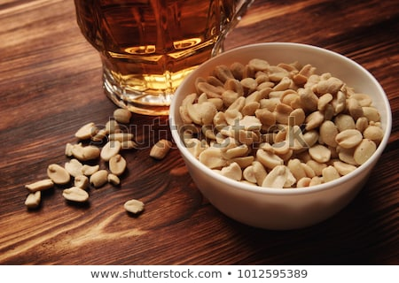Beer with peanuts on old wood table Stock photo © phila54