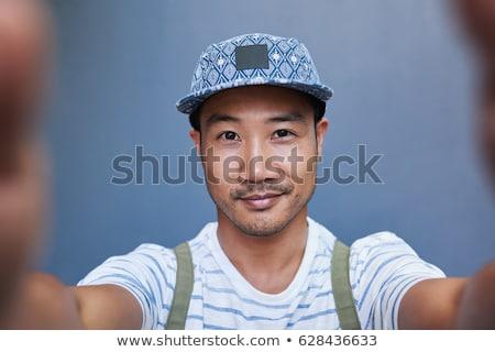Elegáns fiatalember rövidnadrág sapka kint mosoly Stock fotó © Nejron