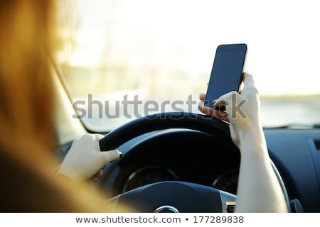 close up of a businesswoman sending a text while driving to work stock photo © deandrobot