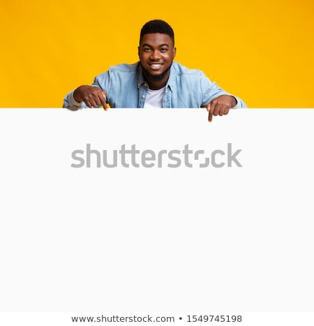 young man pointing at a blank signboard stock photo © nito