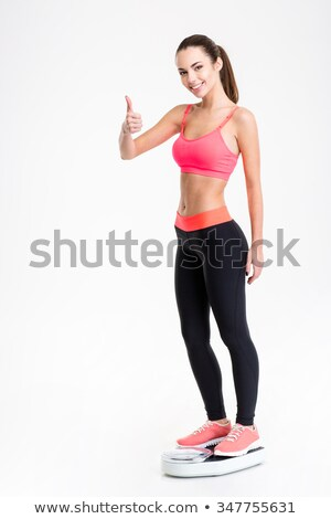 Fitness woman standing on weighing scale and showing thumbs up Stock photo © deandrobot
