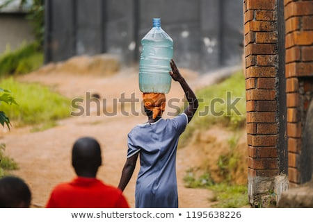 Stock photo: African woman carrying water