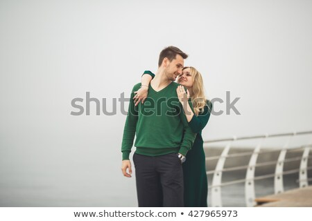 couple in love sitting and kissing at wooden sea pier stock photo © deandrobot