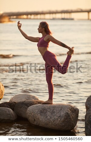 beautiful young woman standing near big stone on the beach in Gr Stock photo © Massonforstock