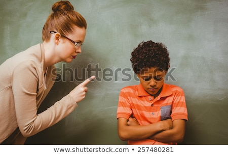 upset young woman standing with arms folded and pointing stock photo © deandrobot